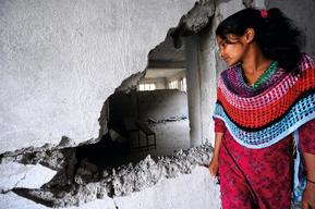 Laxmi Giri, 15, looks into her destroyed classroom of Balefi Secondary School