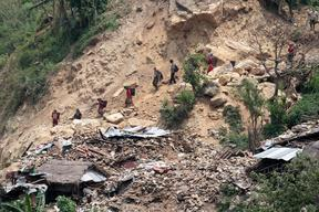 Men and women in Gorkha district walk down a mountain to collect relief items being distributed in Baluwa