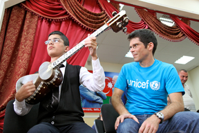 UNICEF Goodwill Ambassador Christoph Hartmann listens to a boy with a visual impairment playing tar