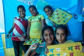 Five young girls show their completed English and Nepali alphabet boards at a UNICEF-supported child-friendly space in Syuchatar