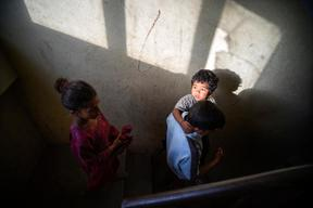 Anju Nepali, 4, is carried downy the stairs of he quake-damaged apartment where they used to live in the town of Charikot