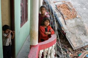 Twin sisters Jamuna, bottom, and Ganga, top, Nepali, 9, pose for a portrait while their little brother