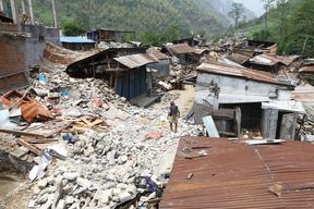 A man walks amid the rubbles of a destroyed house in Baluwa