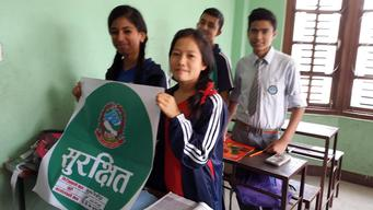 Grade 10 students from Eden Bridge Academy hold the green sticker certifying the safety of their school building