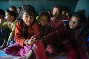 Jamuna Nepali, 9, her sister Ganga, right, share a drink at a UNICEF-supported Child Friendly Space