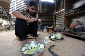 Laxmi Giri, 16, cuts bottle-gourds for meal in her temporary kitchen in Balephi village in Sindhupalchowk