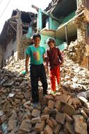 Lucky Maharjan helping his younger sister Nalisha out of their uncle's damaged house in Khokana neighbourhood