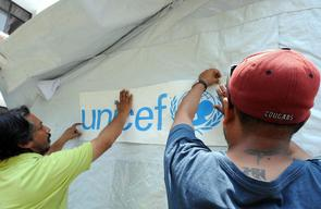 Staff members of Spinal Injury Rehabilitation Center set up UNICEF-provided tent on the premises of the rehab center in Kavrepalanchowk