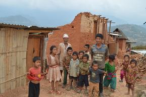 Young children and two men stand in earthquake affected neighborhood in Sitalpati Village Development Committee in Sindhuli